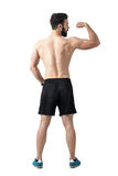 Rear view of young fit athlete flexing arm muscles Stock Images