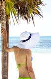 Rear view of young girl in bikini and hat under palm looking on the ocean Royalty Free Stock Photo