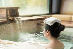 Rear view of young girl enjoy the hot springs. And put a towel on her head while water flows on the background royalty free stock image