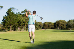 Rear view of young golfer man taking shot. While standing on field royalty free stock photos