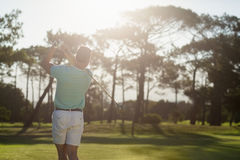 Rear view of young golfer taking shot. On sunny day royalty free stock image