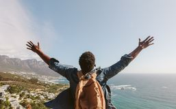 Man enjoying the view from top of mountain. Rear view of young guy with backpack standing outdoors with arms spread open against seascape. Man enjoying the view Royalty Free Stock Photo