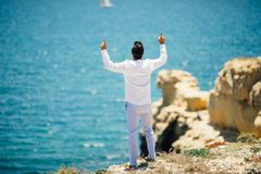 Rear view of Young handsome man pointed up or praying on ocean background stock image