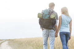 Rear view of young hiking couple holding hands while walking in countryside Royalty Free Stock Images