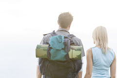 Rear view of young hiking couple standing against clear sky royalty free stock image