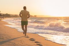 Man running on beach at sunset. Rear view of young jogger running on beach at sunset over sea Stock Photo