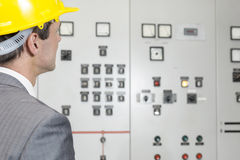 Rear view of young male supervisor examining control room in industry Stock Image