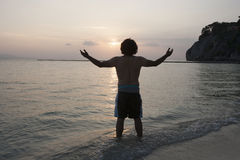 Rear view of young man with arms outstretched on beach at sunset Royalty Free Stock Photography
