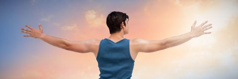 Composite image of rear view of young man with arms outstretched over white background. Rear view of young man with arms outstretched over white background Stock Photography