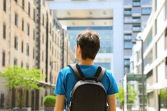 Rear view of a young man with backpack just arrived in a big cit. Y and looking to modern buildings with perspectives and opportunities, Cologne city district stock photo