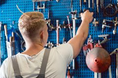 Rear view of a man choosing an useful tool during work in a repair shop. Rear view of a young man choosing an useful tool during work in a modern automobile Royalty Free Stock Photos