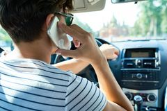 Young Man Speaking by Phone in Car. Rear view of young man driving luxury car and speaking by smartphone, copy space Royalty Free Stock Images