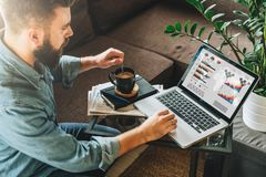 Rear view. Young man, entrepreneur, sits at home on couch at coffee table,drinking coffee,working on laptop with graphs Royalty Free Stock Photos