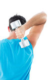 Rear view of a young man exercising with dumbbell Stock Photo