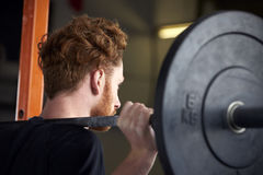 Rear View Of Young Man In Gym Lifting Weights On Barbell Stock Image