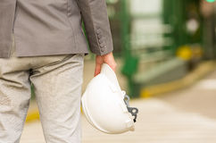 Rear view of young man holding construction helmet Royalty Free Stock Photo
