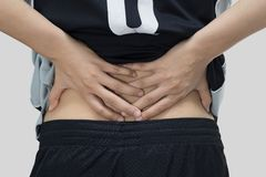 Rear view - A young man holding his back in pain stock images