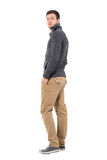 Rear view of young man in jumper with hands in pockets smiling at camera. Stock Photography