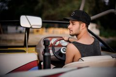 Rear view young man looking into the distance in the motorboat. Rear view young man in the dark cap looking into the distance sitting in the motorboat on the stock photo