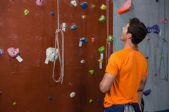 Rear view of young man looking up while standing by climbing wall. At gym Stock Images