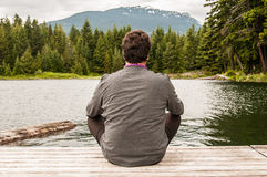 Young man meditating by a lake Royalty Free Stock Image