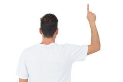 Rear view of a young man pointing upwards Stock Photos