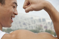Rear view of young man smiling and flexing his bicep Stock Images