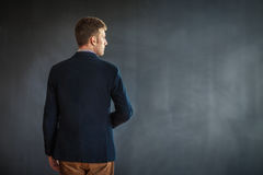 Rear view of young man standing against grey wall background Stock Photos
