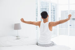 Rear view of a young man stretching arms in bed Royalty Free Stock Images