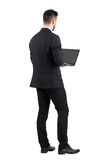 Rear view of young man in suit using laptop Royalty Free Stock Images