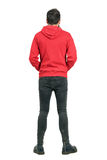 Rear view of young man in tight jeans and boots wearing red hoodie. Full body length portrait isolated over white studio background Stock Images