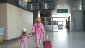 Rear view of young mother and cute daughter holding hands at the airport and watching flight schedule stock footage