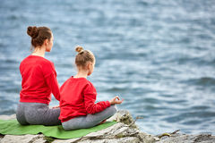 Rear view of young mother and daughter doing yoga exercises on the stone near the river. Beautiful mother and daughter in the sportwear and barefoot. Beautiful Royalty Free Stock Photos