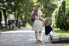 Rear view of young mother walking with little girl daughter in. Beautiful summer park, wearing fasionable dress clothes Royalty Free Stock Images