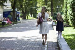 Rear view of young mother walking with little girl daughter in. Beautiful summer park, wearing fasionable dress clothes Stock Photos