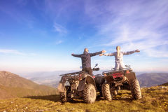 Rear view of young pair near atv. Man is showing something in distance to her girlfriend. Stock Photo