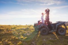 Rear view of young pair near atv. Man is showing something in distance to her girlfriend. Stock Images