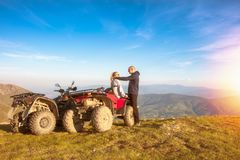 Rear view of young pair near atv. Man is showing something in distance to her girlfriend. Stock Photos