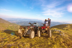Rear view of young pair near atv. Man is showing something in distance to her girlfriend. Stock Image