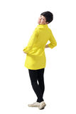 Rear view of young playful woman wearing yellow coat turning and smiling at camera Stock Images