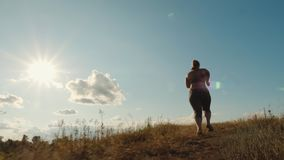 Plus size girl runs up the hill. Rear view: young plus size girl runs up the hill in the early morning. Concept of losing weight with exercise for health. Slow stock video