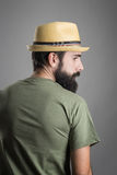 Rear view of young serious bearded man with straw hat looking away Stock Photo