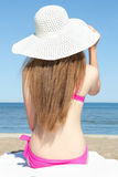 Rear view of young slim woman in bikini sitting on sandy beach Royalty Free Stock Images