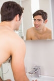 Rear view of a young smiling at self in bathroom mirror Stock Images