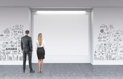 Businessman businesswoman looking at mockup poster. Rear view of young and successful business partners wearing suits looking at a blank horizontal mock up Royalty Free Stock Photo