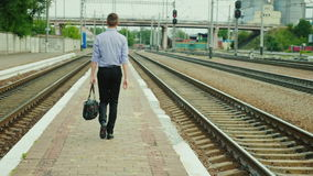 Rear view: A young successful businessman walks along the railway station along the tracks. He carries a bag in his hand. A young successful businessman walks stock footage