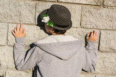 Rear view of young teen girl in gray jacket  standing next to th. Back view of young teen girl in gray jacket  standing next to the stone grey wall. Concept Royalty Free Stock Images