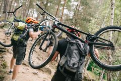 Rear view of young trial bikers carrying bikes on backs at forest. And going uphill stock images