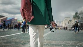 Unrecognizable young woman with camera walking in Moscow, Kremlin summer. Rear view of a young unrecognizable woman walking in Moscow near Kremlin holding camera stock video footage