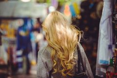 Rear view of a young woman with a beautiful blonde straight long hair in motion in a city in a hurry.  Stock Image